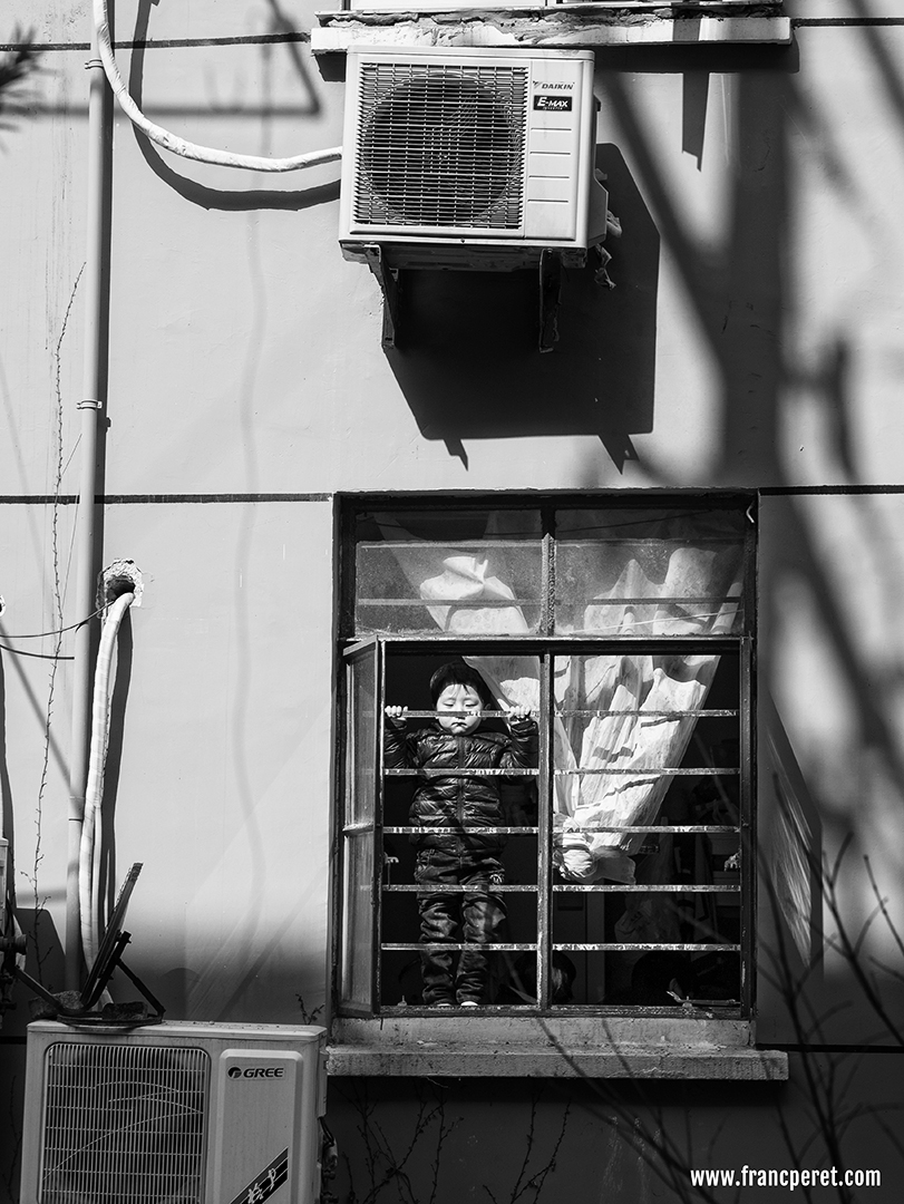 Kids behind the fence. I was attracted by 2 common point:<br />  1- the round face of the kid and the round shape of the air conditioner fan on top of him.<br /> 2 - His straight and symmetric posture compare to the straight lines (tube, pipe, fence, window, shadows) surrounding him.