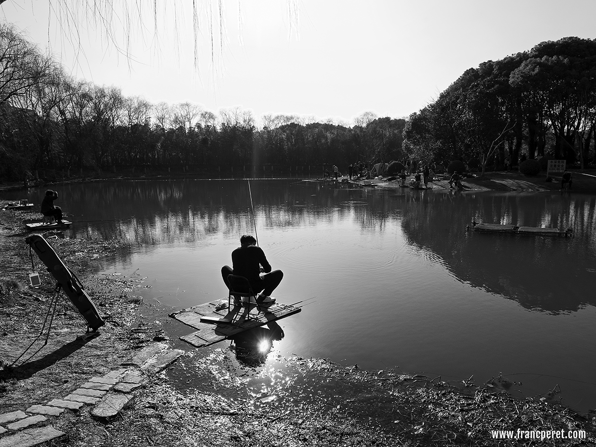 Fisherman in Shanghai Century Park. Path way (dam), lake shape and man posture altogether create motion in the shot even nothing much is happening.